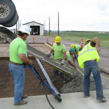 Men working on concrete slab being poured from concrete machine